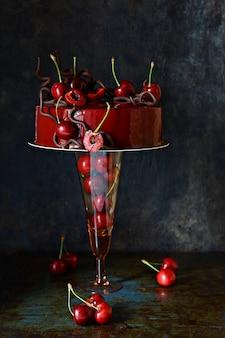 Ciasto czekoladowe z musem z czarnego lasu z czerwoną polewą lustrzaną i świeżymi wiśniami
