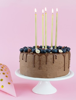 Ciasto czekoladowe z orzechami jagodowymi i świeczkami na białym wysokim talerzu na różowym tle