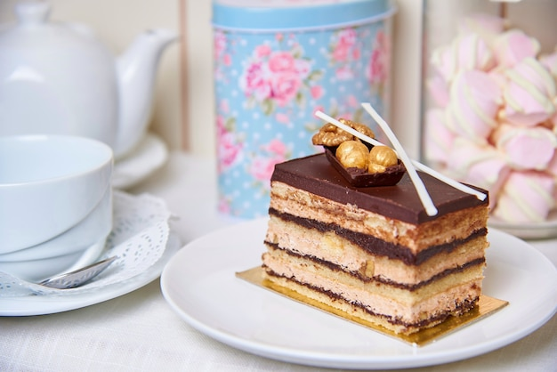Ciasto czekoladowe z orzechami na talerzu w pobliżu filiżanki, czajnik i słoik marshmallows.