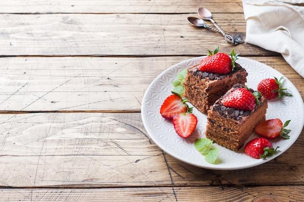Ciasto czekoladowe z truskawkami i miętą. drewniany stół. skopiuj miejsce