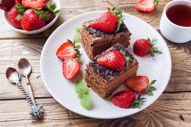 Ciasto czekoladowe z truskawkami i miętą. drewniany stół.
