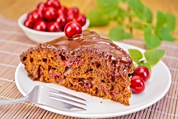 Ciasto czekoladowe z wiśniami na talerzu, wiśniami, miętą na bambusowej serwetce na tle drewnianych desek