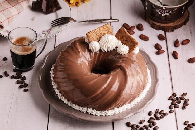 Ciasto czekoladowo-kawowe z filiżanką kawy na drewnianym stole