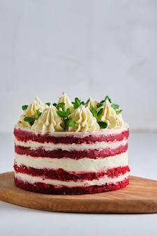 Ciasto czerwony aksamit. deser udekorowany kremem serowym i listkami mięty. czerwone ciasto z malinową warstwą w środku.
