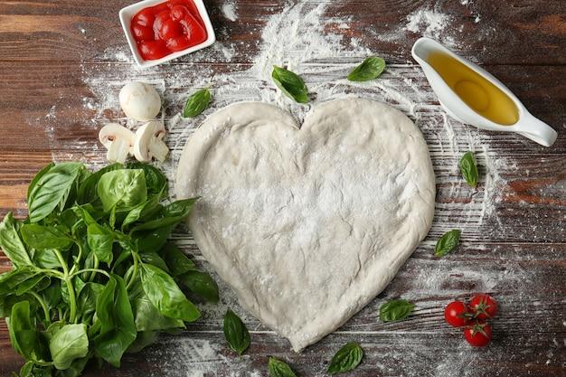 Ciasto do pizzy w kształcie serca ze składnikami na stole
