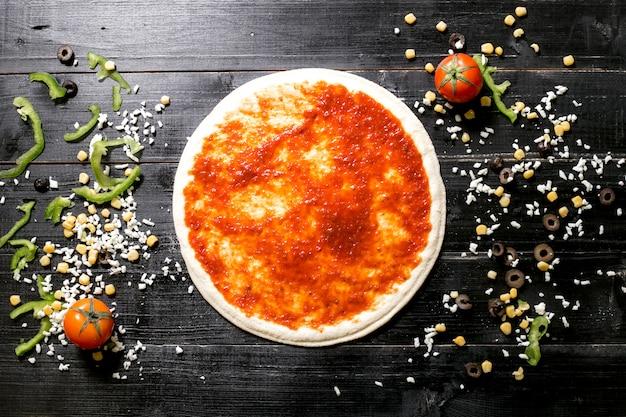 Ciasto do pizzy z sosem pomidorowym obok sera posypuje pomidorową papryką kukurydzianą