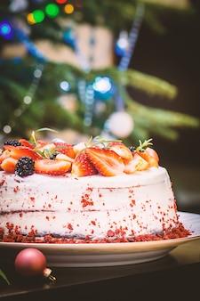 Ciasto domowe red velvet ozdobione kremem i jagodami na tle bożego narodzenia