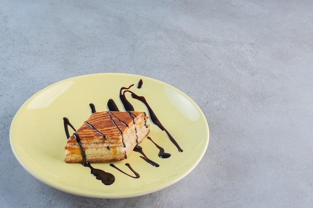 Ciasto domowej roboty ozdobione czekoladą na żółtym talerzu.
