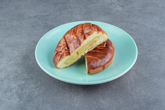 Ciasto domowej roboty pokrojone na pół na niebieskim talerzu.