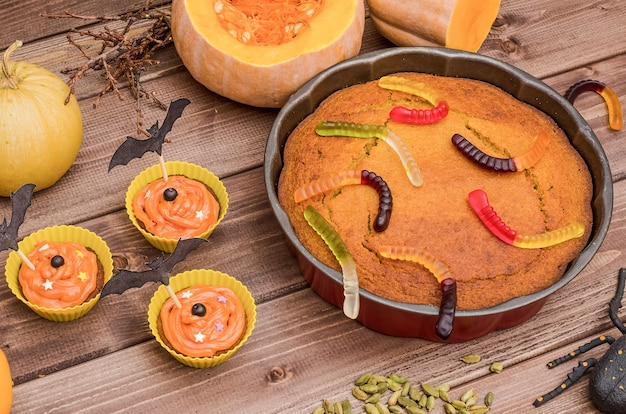 Ciasto dyniowe i babeczki na halloween z dyniami, ozdobione słodyczami na drewnianej powierzchni