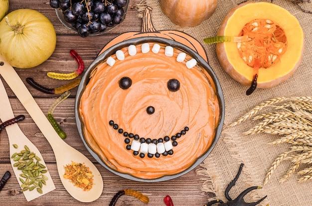 Ciasto dyniowe na halloween z dyniami, ozdobione słodyczami na drewnianej powierzchni