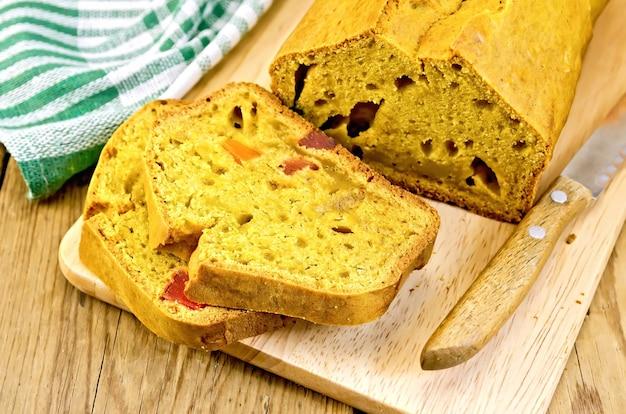 Ciasto dyniowe z kandyzowanymi owocami na desce, nóż, serwetka na tle drewnianych desek
