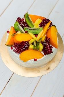 Ciasto egzotyczne biszkopt z białą śmietaną i dużą ilością owoców (kiwi, granat, persimmon, mango)