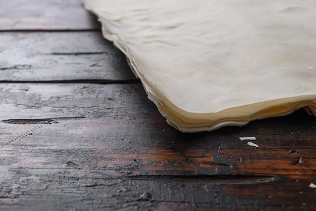 Ciasto filo do gotowania na starym ciemnym drewnianym stole.