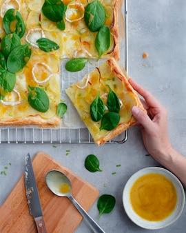 Ciasto francuskie z ziemniakami, serem, szpinakiem i miodem i winegretem musztardowym na ruszcie i dnie z szarego cementu