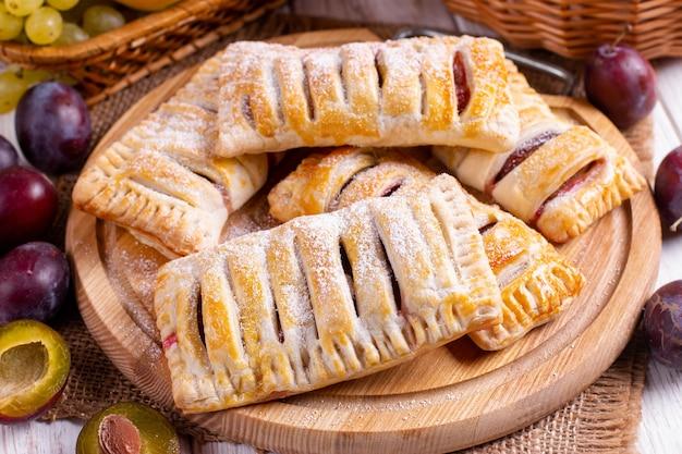 Ciasto francuskie ze śliwkami na deser na drewnianym stole
