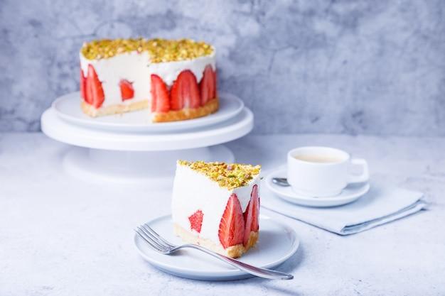 Ciasto freesier ze świeżymi truskawkami i pistacjami. francuski klasyczny deser. porcja ciasta na zbliżenie biały talerz.