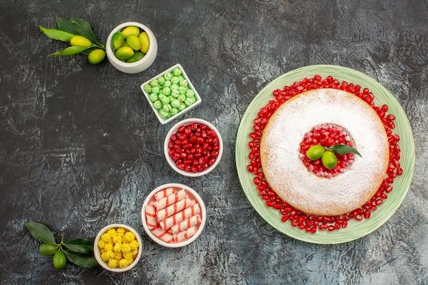 Ciasto granatowe z pestkami granatu miski limonek różne słodycze