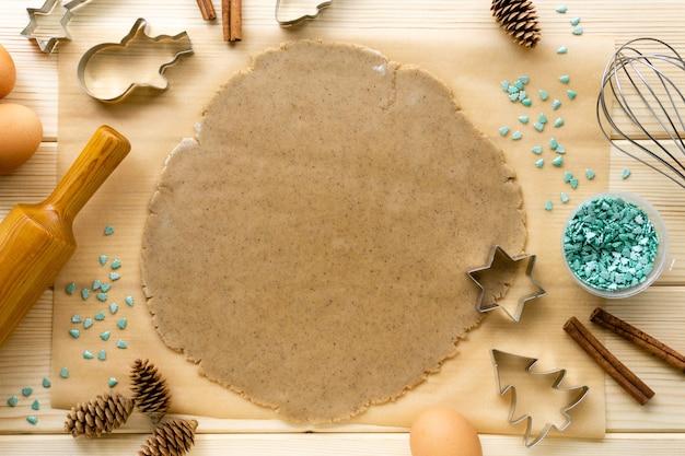 Ciasto i formy na świąteczne ciasteczka ze słodką posypką na drewnianej