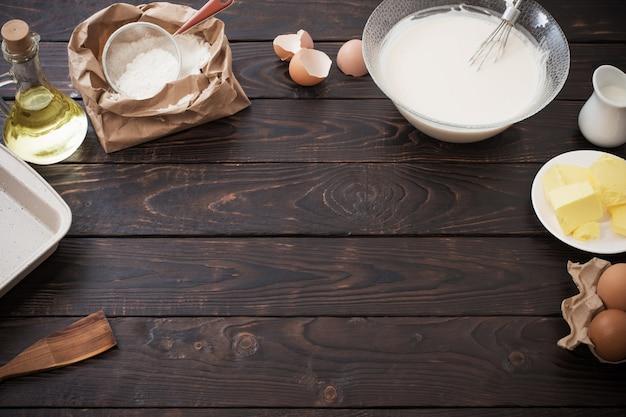 Ciasto i produkty do jego przygotowania na ciemnym tle drewnianych