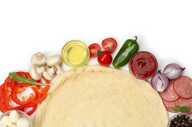 Ciasto i składniki do gotowania pizzy na białym tle