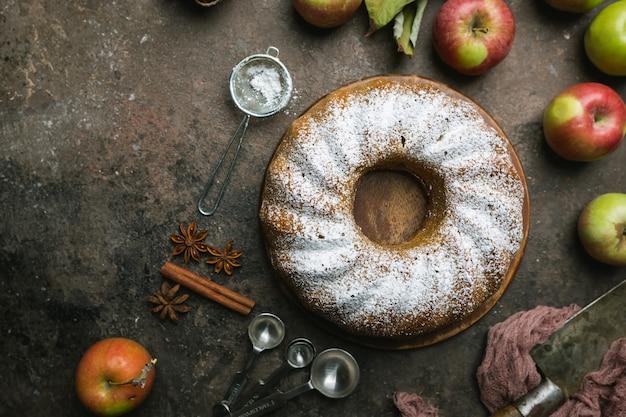 Ciasto jabłkowe w stylu rustykalnym posypane cukrem pudrem na starym drewnianym stole
