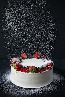 Ciasto jagodowe z cukrem pudrem na ciemnym stole