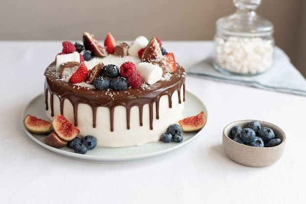 Ciasto jagodowe z czekoladowym ganache na białym obrusie koncepcja urodzinowego dnia matki