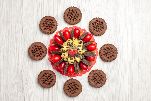 Ciasto jagodowe z widokiem z góry na czerwonej owalnej serwetce i ciasteczka na białym drewnianym stole
