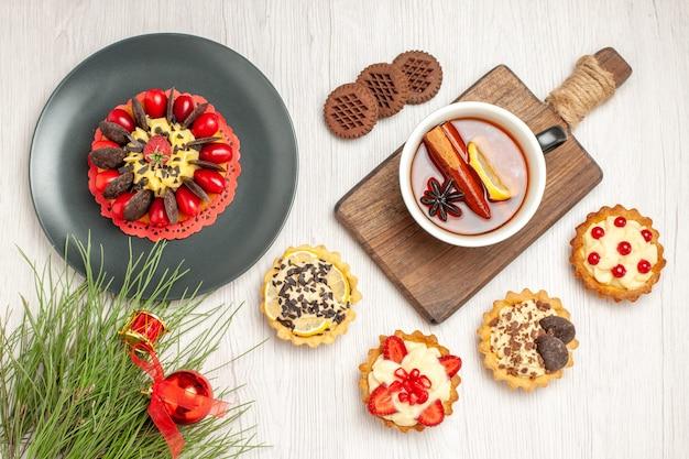 Ciasto jagodowe z widokiem z góry na szarym talerzu tarty filiżankę cytrynowo-cynamonowej herbaty na desce do krojenia ciasteczka i liście sosny na białym drewnianym podłożu