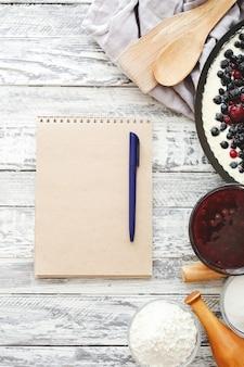 Ciasto jagodowe z wiśnią, porzeczką, jeżyną, jagodą z naczyniami i makietą przepisu na białym drewnianym stole. makieta widok z góry sernik
