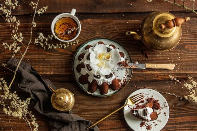Ciasto kakaowe i filiżanka herbaty z czajnik na drewnianym stole