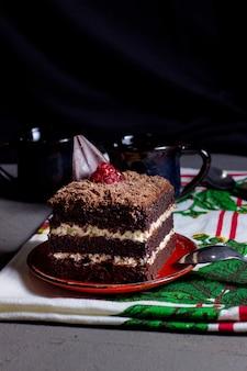 Ciasto kakaowe z białą śmietaną przyozdobioną startą czekoladą i malinami