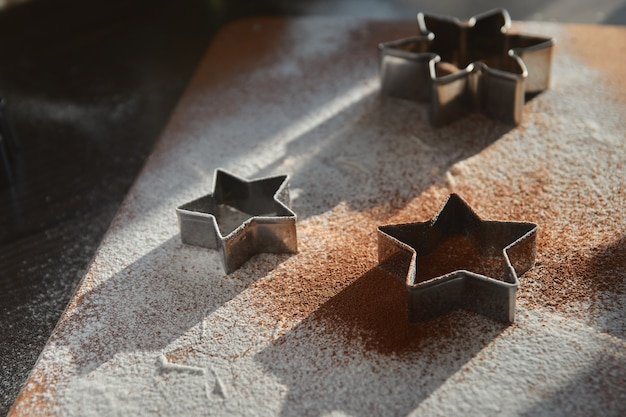 Ciasto kruche na pierniki zawijane na desce. wycinanie gwiazdy. koncepcja tradycji noworocznych i proces gotowania. ciasteczka na ciemnobrązowym drewnianym stole. tworzenie rodziny