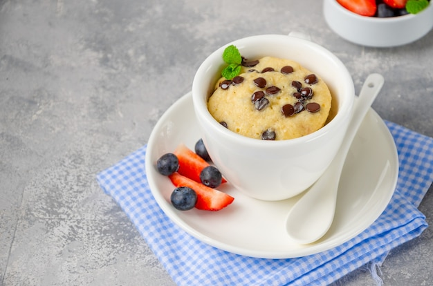 Ciasto kubek z kawałkami czekolady, świeżymi jagodami i śmietaną na szarym tle betonu. skopiuj miejsce.