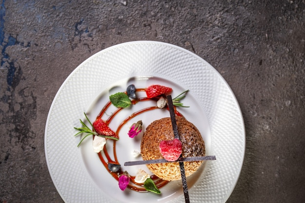 Ciasto kurabye na białym talerzu z jagodami widok z góry
