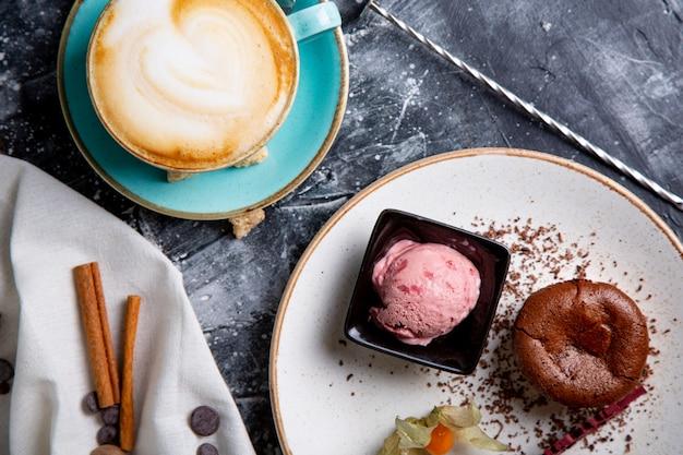 Ciasto lawowe czekoladowe stopione z lodami na talerzu i cappuccino. kulki lodów w filiżance. ciemne czarne tło.