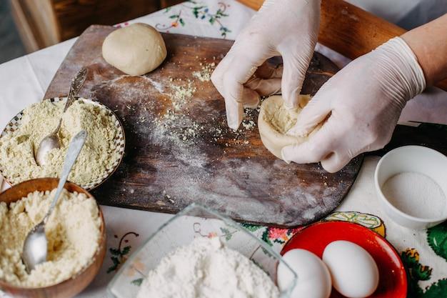 Ciasto mączka mięsna ciasto w trakcie robienia ciasta gotować jajka z mąki na rustykalnym biurku z brązowego drewna