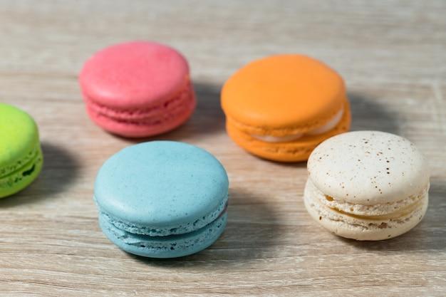 Ciasto makaronik lub makaroniki na tle stołu z drewna, słodki i kolorowy deser