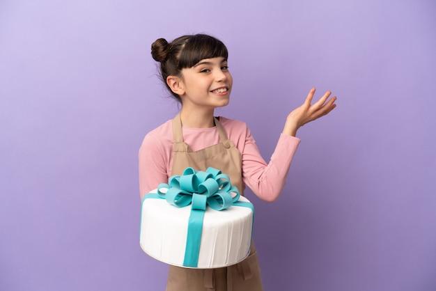 Ciasto mała dziewczynka trzyma duży tort na białym tle na fioletowej ścianie wyciągając ręce na bok, by zachęcić do przyjścia