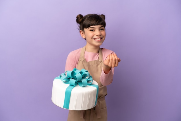 Ciasto mała dziewczynka trzyma duży tort na białym tle na fioletowej ścianie zaprasza do przyjścia z ręką. cieszę się, że przyszedłeś