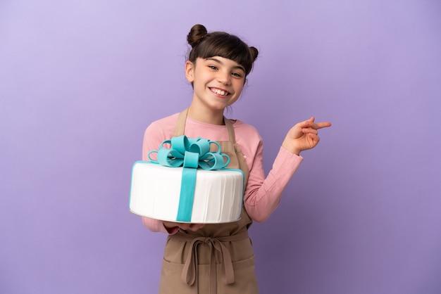 Ciasto Mała Dziewczynka Trzyma Duży Tort Na Białym Tle Na Fioletowym Palcem Wskazującym Z Boku Premium Zdjęcia