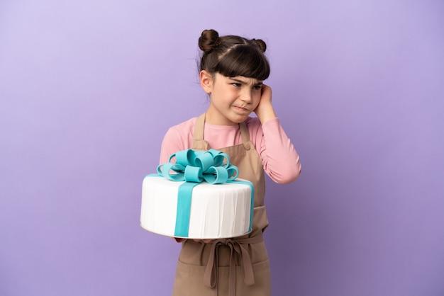 Ciasto mała dziewczynka trzyma duży tort na białym tle na fioletowym tle sfrustrowana i zakrywające uszy