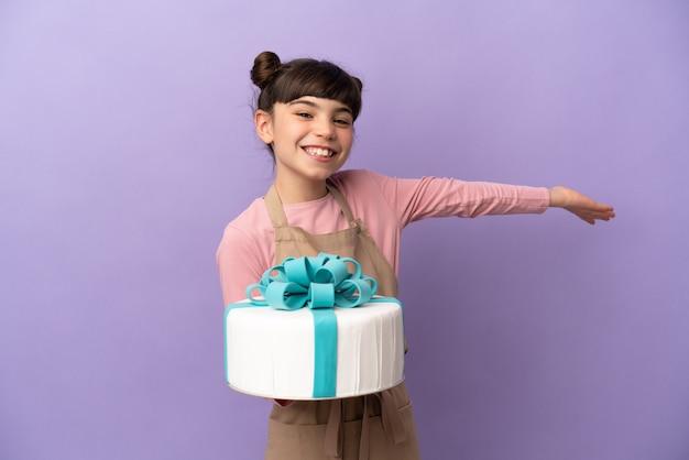 Ciasto mała dziewczynka trzyma duży tort na białym tle na fioletowym tle wyciągając ręce na bok za zaproszenie do przyjścia