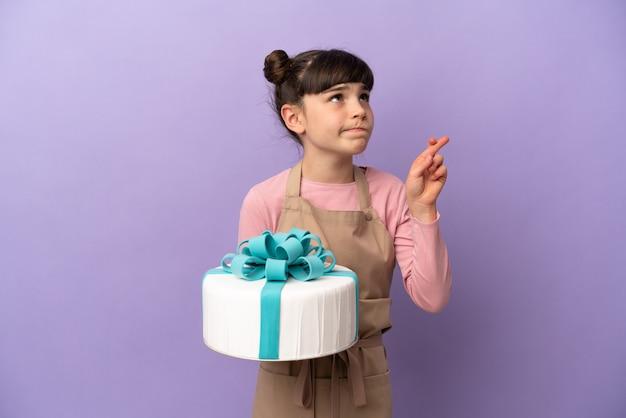 Ciasto mała dziewczynka trzyma duży tort na białym tle