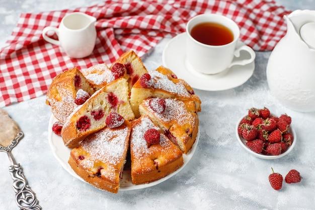 Ciasto malinowe z cukrem pudrem i świeżymi malinami na świetle. letni deser jagodowy.