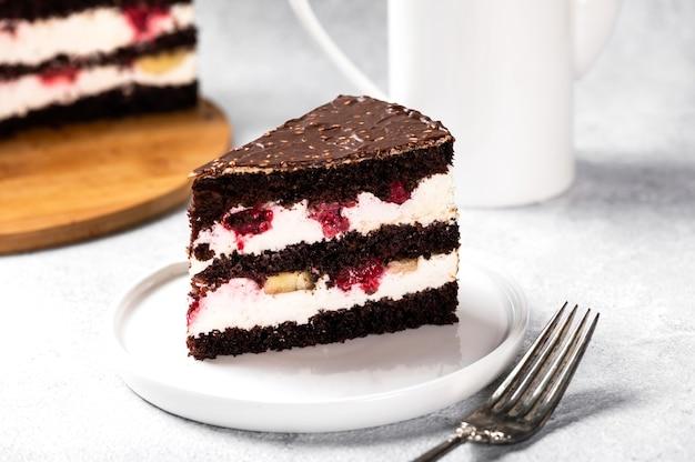 Ciasto malinowe z czekoladą. ciasto czekoladowe z jagodami. kawałek ciasta na talerzu. deser na białej powierzchni. ciasto szwarcwaldzkie.