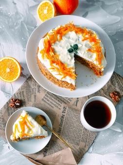 Ciasto marchewkowe na białym talerzu z na pół pokrojoną pomarańczą i filiżanką kawy na jasnym marmurowym tle