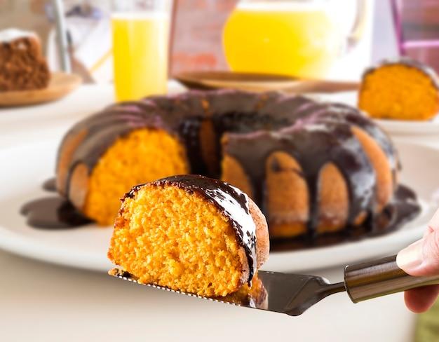 Ciasto marchewkowe z czekoladą i plasterkiem na stole.