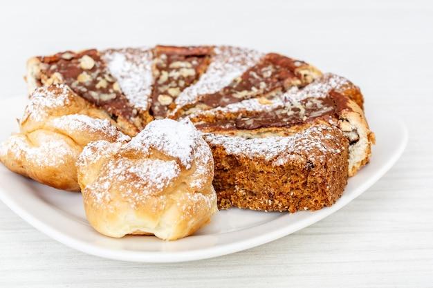 Ciasto marchewkowe z orzechami włoskimi, śliwkami i suszonymi morelami na białej powierzchni drewna